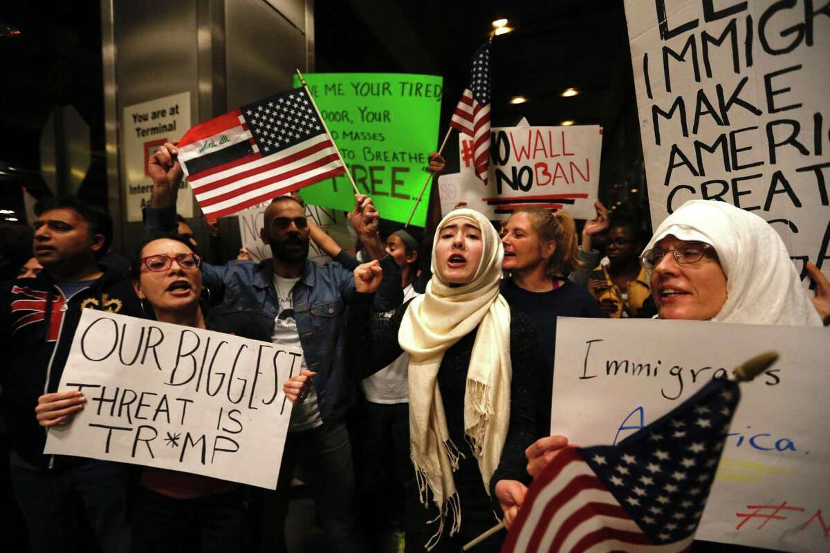 Demonstrators protest anti-immigrant policies and a Muslim travel ban instituted via executive order by the Trump administration as they fill the international arrivals area at George Bush Intercontinental Airport on Sunday, Jan. 28, 2017, in Houston.