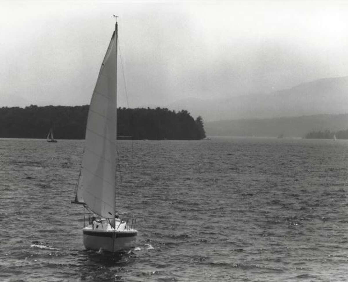 Sailboat cruises across Lake George in New York. Undated