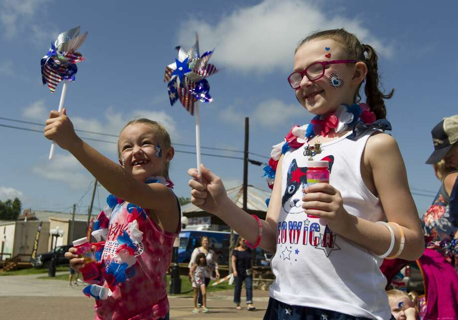 Payton Thomas, left, laughs as her pinwheel spins beside Sophie Willis as they stand in front of a cooling fan during the Montgomery Fourth of July parade, Saturday, July 6, 2019, in Montgomery. Photo: Jason Fochtman/Staff Photographer
