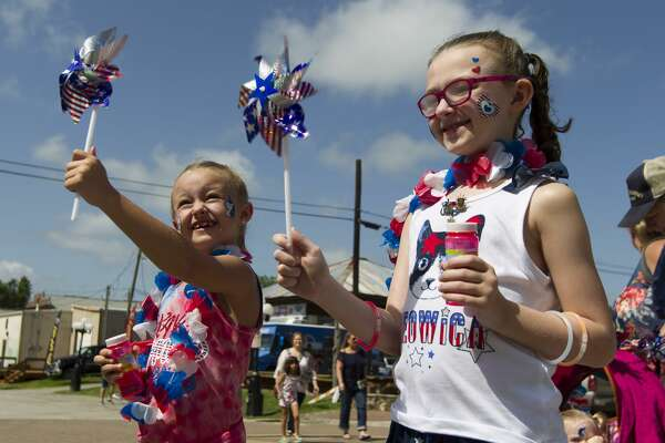 Payton Thomas, left, laughs as her pinwheel spins beside Sophie Willis as they stand in front of a cooling fan during the Montgomery Fourth of July parade, Saturday, July 6, 2019, in Montgomery.