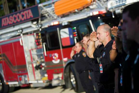 The Atascocita Volunteer Fire Department salutes as the flags are raised during a 9/11 remembrance ceremony Sept. 11, 2014, at Atascocita High School.