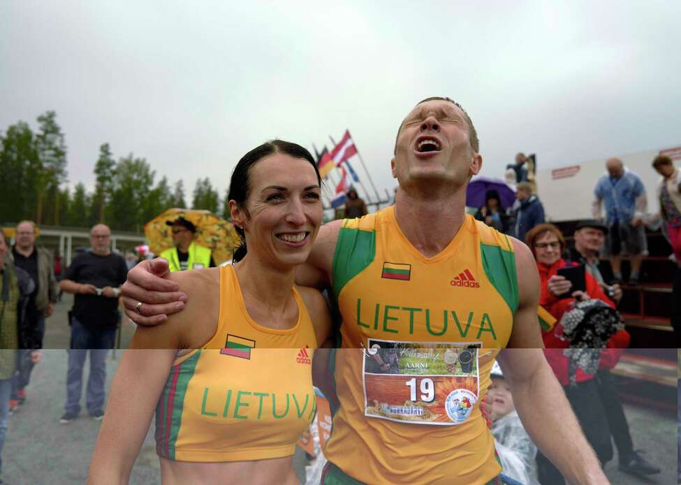 Lithuanian couple Vytautas Kirkliauskas, right, and Neringa Kirkliauskiene celebrate their victory in the wife carrying race, a 278-yard obstacle course, during the 24th world championships in Sonkajarvi, Finland, Saturday, July 6, 2019. Despite the event's name couples don't have to be married, and organizers say male contestants could
