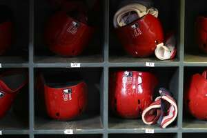 Los Angeles Angels starting players's gloves and helmets are placed in dugout during practice at Minute Maid Park on Friday, July 5, 2019, in Houston.