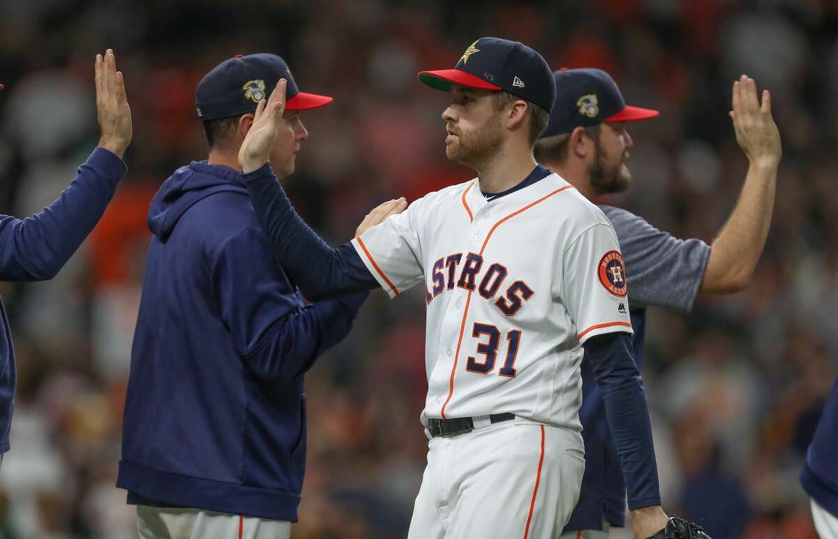 Houston Astros relief pitcher Collin McHugh (31) gives high-fives after closing out the 9th inning of an MLB baseball game at Minute Maid Park Saturday, July 6, 2019, in Houston.