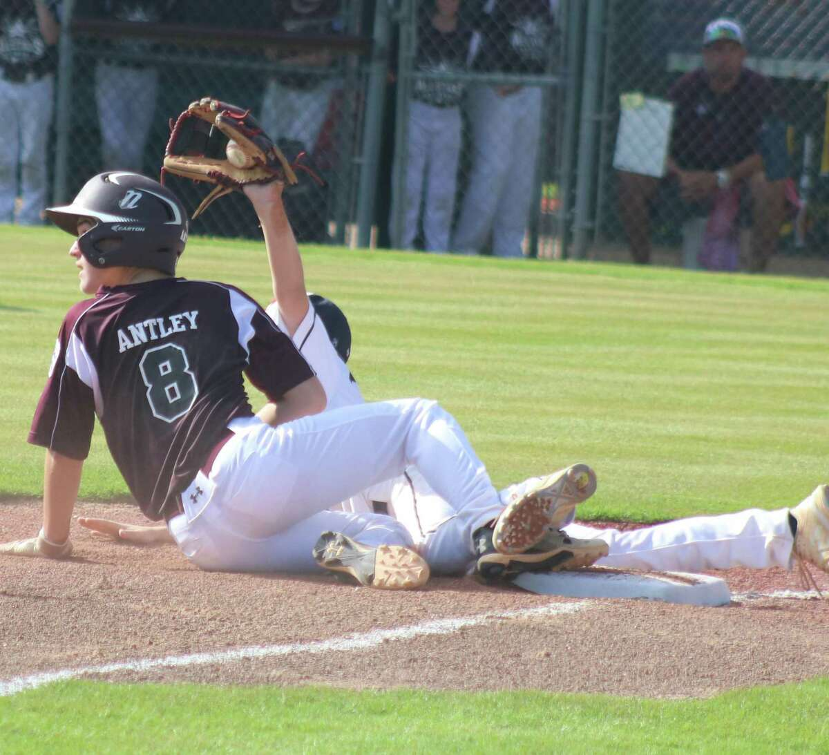 Post Oak's third baseman shows the umpire the ball that led to League City National runner Teague Antley getting called out. Antley was attempting to advance on a pitch in the dirt that didn't roll far from the plate.