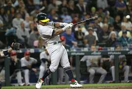 Oakland Athletics' Khris Davis drives in a run on a single against the Seattle Mariners in the seventh inning of a baseball game Friday, July 5, 2019, in Seattle. (AP Photo/Elaine Thompson)