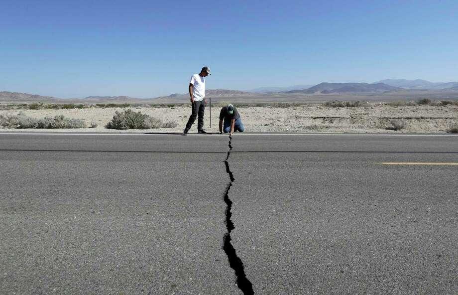 Ron Mikulaco, derecha, y su sobrino Brad Fernández examinan una grieta causada por un sismo sobre la carretera 178, el sábado 6 de julio de 2019, en las afueras de Ridgecrest, California. Photo: Marcio José Sánchez /Associated Press / Copyright 2019 The Associated Press. All rights reserved.