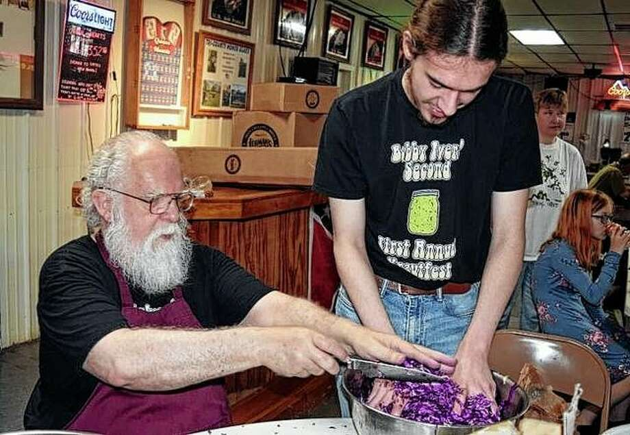 Eric Ivers (left) and his grandson Jake Foiles prepare kraut Saturday during the Bobby Ivers Krautfest.