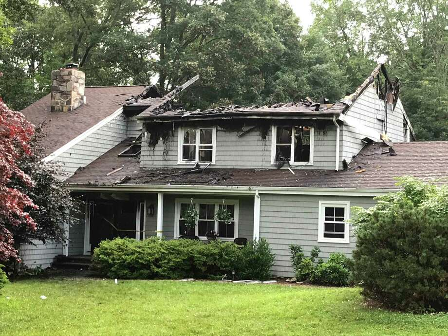 A house on Country Way in Bethel was destroyed in a fire on Saturday, July 6, 2019. The morning after the fire, the windows were smashed and a strip of yellow police tape blocked the front door. The roof in the center of the house was gone. Photo: Julia Perkins / Hearst Connecticut Media / The News-Times