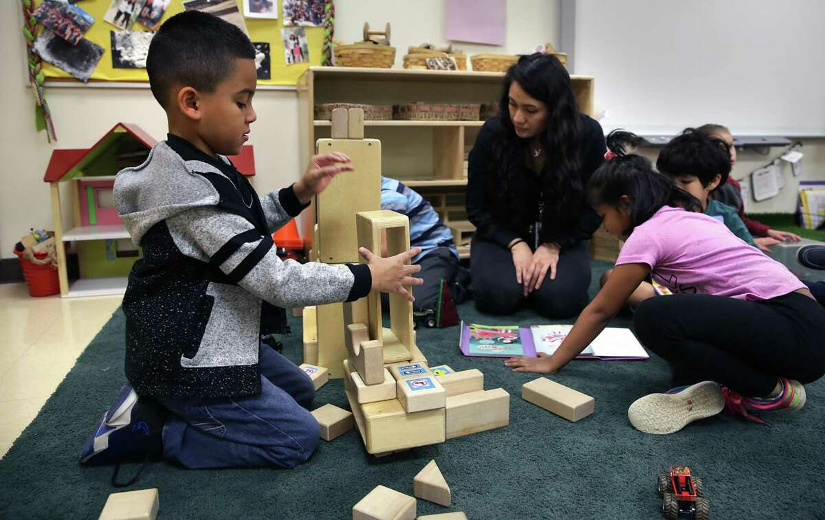 Jonathon Carmona, left, builds with blocks as teacher Alejandra Sanchez reads with other students at the Pre-K 4 SA North Center in 2019.