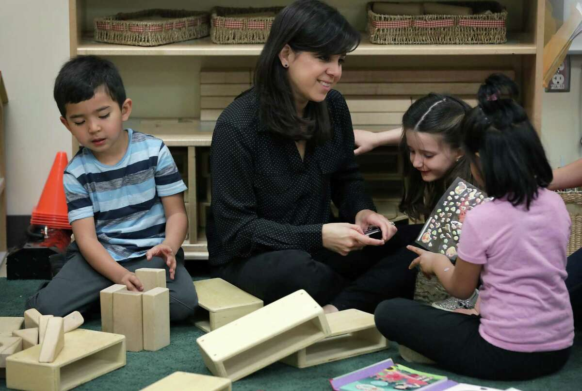 Lilyann Cazares-Mezquiti, a teacher at Pre-K 4 SA North Center, plays with two girls as Gabriel Carlos builds with blocks in 2019.