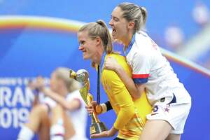 Alyssa Naeher and Morgan Brian, right, celebrate with the FIFA Women's World Cup Trophy following Sunday's win over the Netherlands.