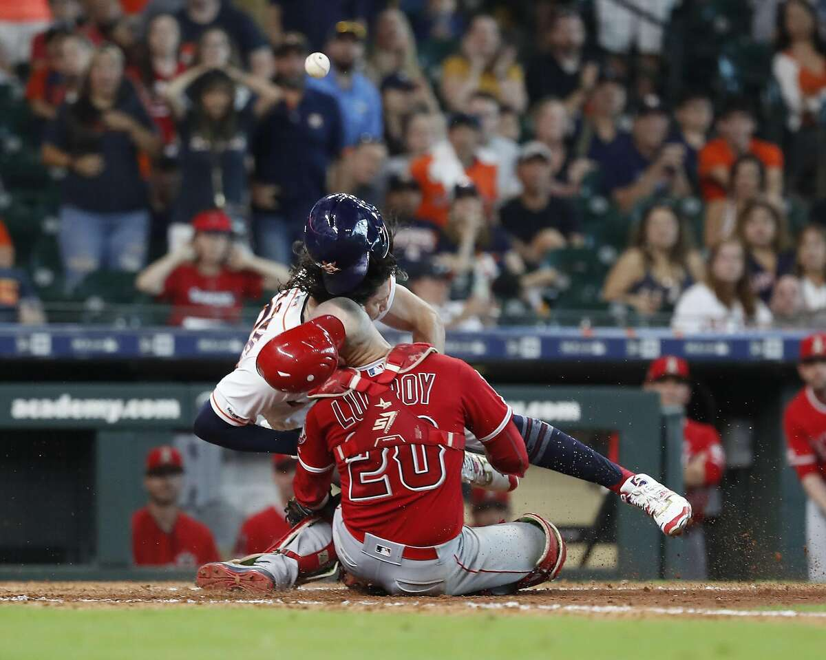 Los Angeles Angels catcher Jonathan Lucroy (20) and Astros runner Jake Marisnick collide at home during the eighth inning Sunday at Minute Maid Park. Marisnick was called out on the play