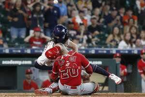 Los Angeles Angels catcher Jonathan Lucroy (20) and Houston Astros Jake Marisnick (6) collide at home during the eighth inning of an MLB game at Minute Maid Park, Sunday, July 7, 2019, in Houston.