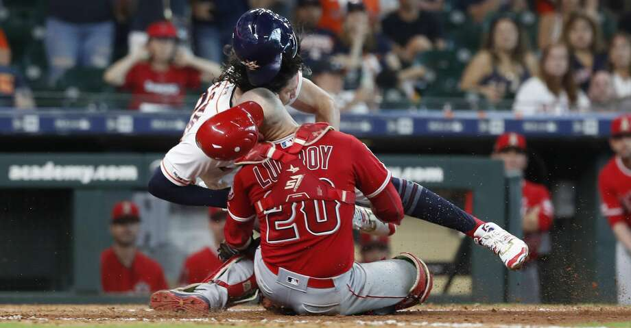 Los Angeles Angels catcher Jonathan Lucroy (20) and Houston Astros Jake Marisnick (6) collide at home during the eighth inning of an MLB game at Minute Maid Park, Sunday, July 7, 2019, in Houston. Photo: Karen Warren/Staff Photographer