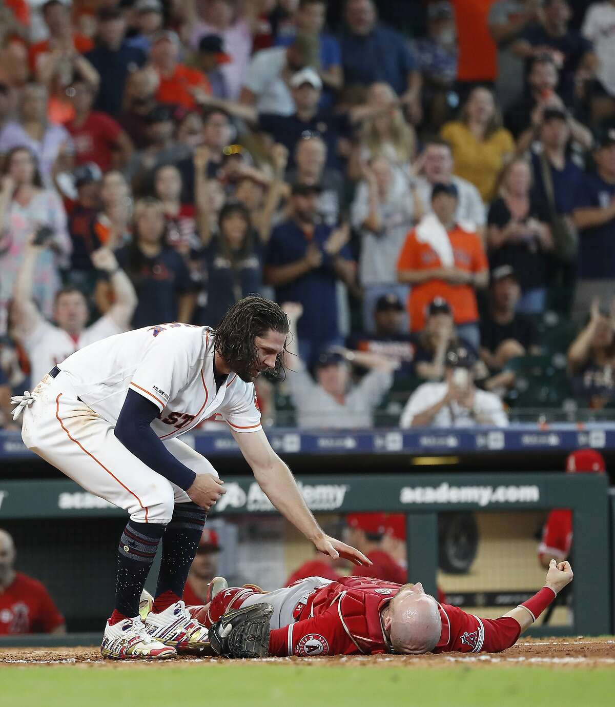 Houston Astros Jake Marisnick (6) checks on Los Angeles Angels catcher Jonathan Lucroy (20) after Lucroy was injured as they collided at home during the eighth inning of an MLB game at Minute Maid Park, Sunday, July 7, 2019, in Houston.