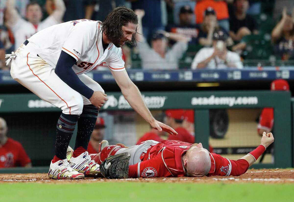 Astros outfielder Jake Marisnick checks on Jonathan Lucroy after plowing into the Angels catcher in Sunday's eighth inning at Minute Maid Park. Lucroy was taken to a Houston hospital, where he was being evaluated for a possible concussion and broken nose.