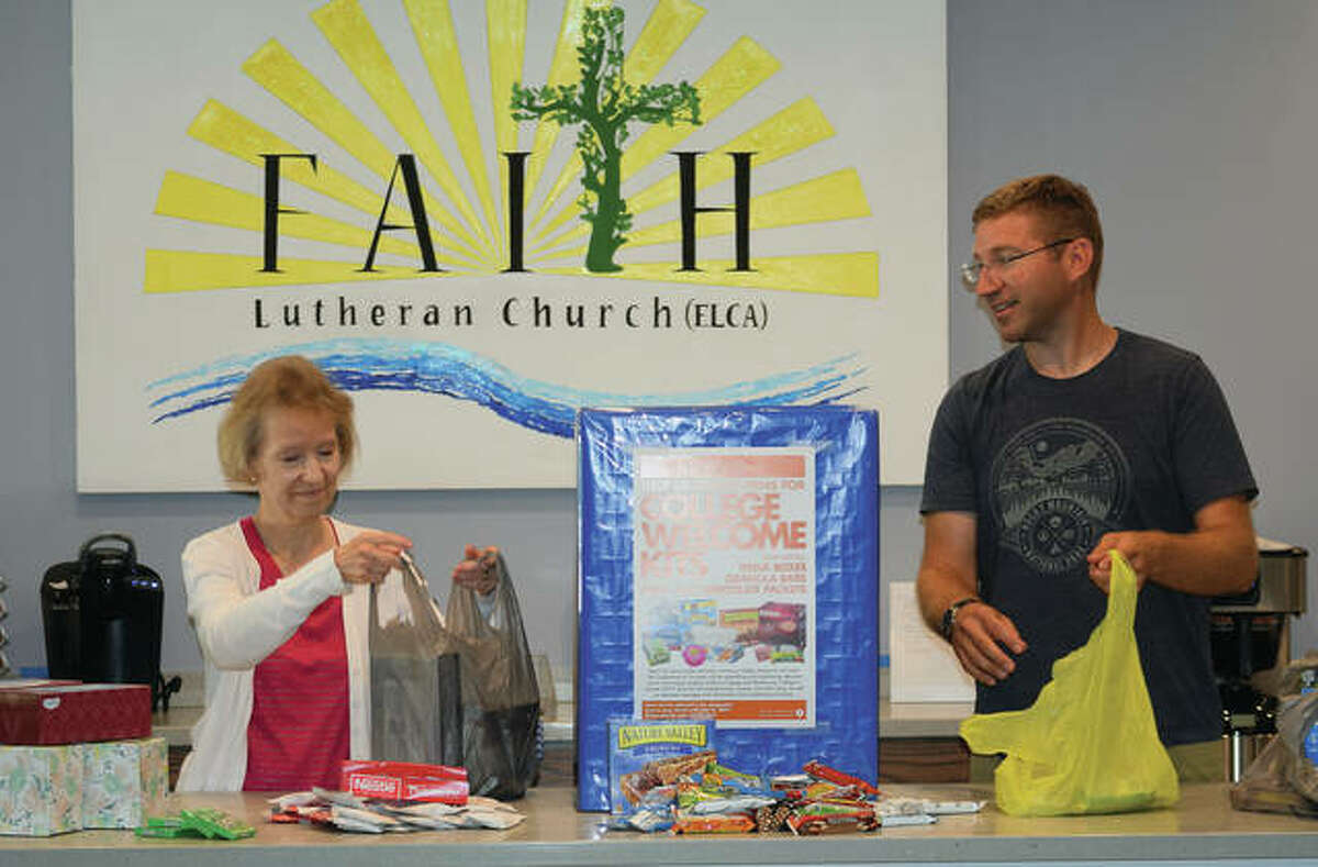 Parish secretary Kris Roth (left) and Faith Lutheran Church Pastor Adam Dichsen organize supplies that will go in kits for college freshmen and transfer students.
