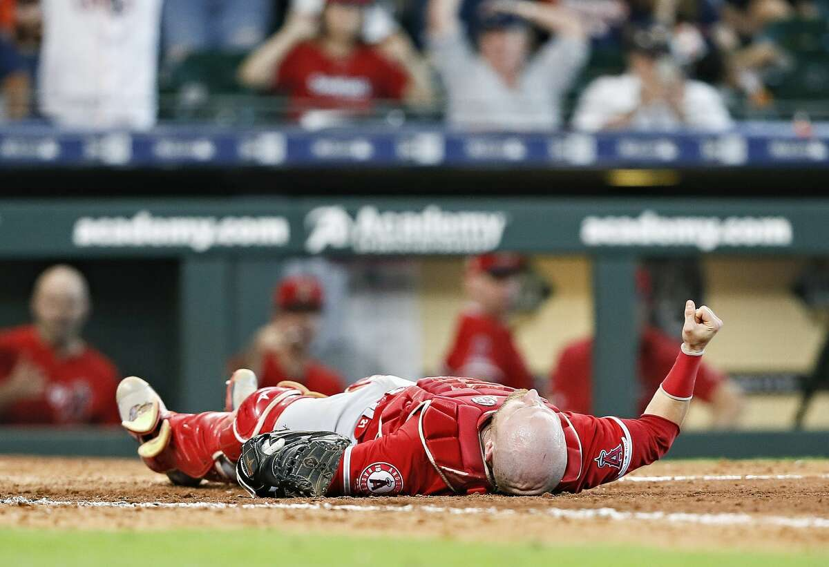 HOUSTON, TEXAS - JULY 07: Jonathan Lucroy #20 of the Los Angeles Angels of Anaheim lays at home plate after a collision with Jake Marisnick #6 of the Houston Astros who was attempting to score in the eighth inning at Minute Maid Park on July 07, 2019 in Houston, Texas.