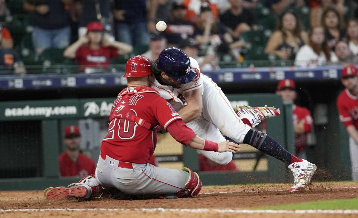Houston Astros' Jake Marisnick, right, collides Los Angeles Angels catcher Jonathan Lucroy (20) while trying to score during the eighth inning of a baseball game Sunday, July 7, 2019, in Houston. Marisnick was called out under the home plate collision rule.