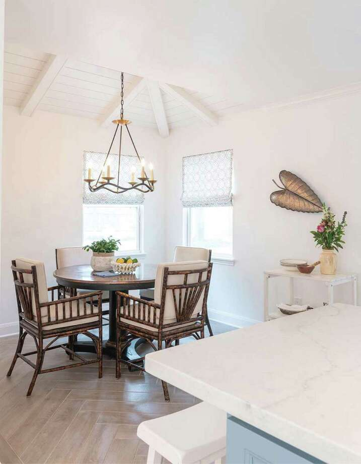 Window shades and a vaulted ceiling open up this dining space.