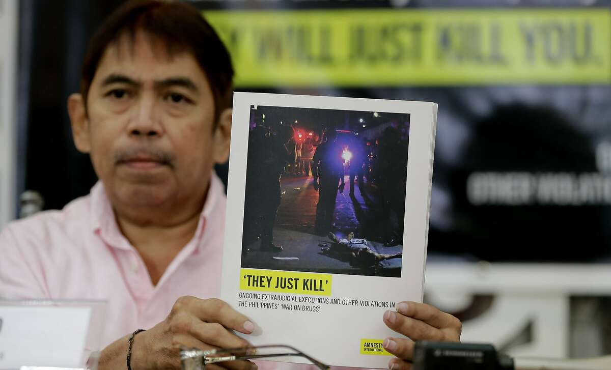 Butch Olano, Amnesty International Section Director in the Philippines, holds a copy of the Amnesty's report during a news conference, Monday, July 8, 2019, in Manila, Philippines. Amnesty International has urgently called for international pressure and an immediate U.N. investigation to help end what it says are possible crimes against humanity in the Philippine president's bloody anti-drug crackdown. (AP Photo/Bullit Marquez)