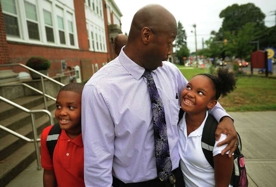 Siblings Trevor and Simone Good get hugs from Principal Sherrod McNeill as they return for the first day of school at Franklin School in Stratford, Conn. on Thursday, September 1, 2016. Photo: Brian A. Pounds / Hearst Connecticut Media / Connecticut Post