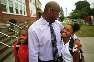 Siblings Trevor and Simone Good get hugs from Principal Sherrod McNeill as they return for the first day of school at Franklin School in Stratford, Conn. on Thursday, September 1, 2016.