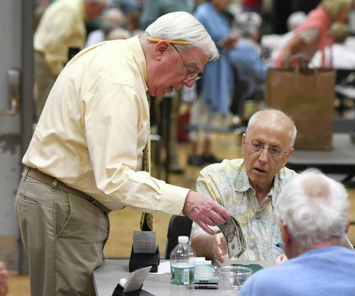 Organizer Steve Becker collects money from participants playing bridge at the YWCA in Greenwich.