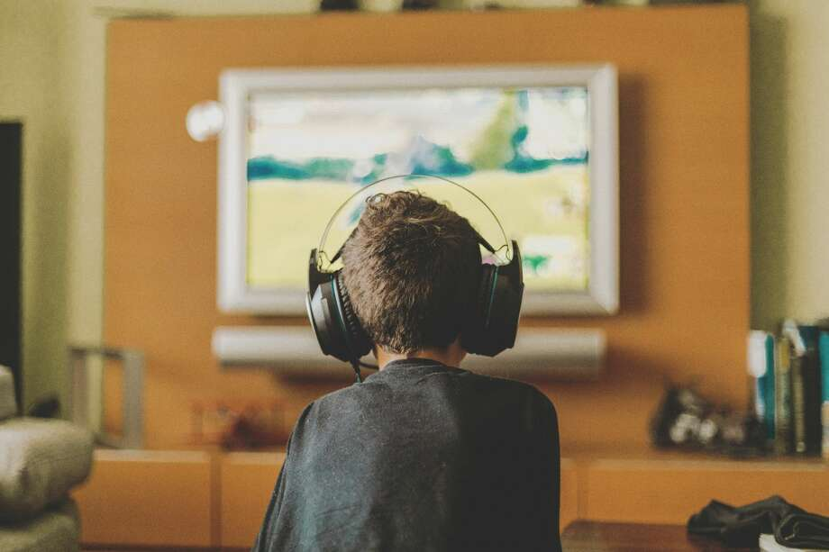 boy enjoying game console at home.Natural light  A couple are worried about their grandson who appears to be addicted to video games. Photo: Carol Yepes/Getty Images
