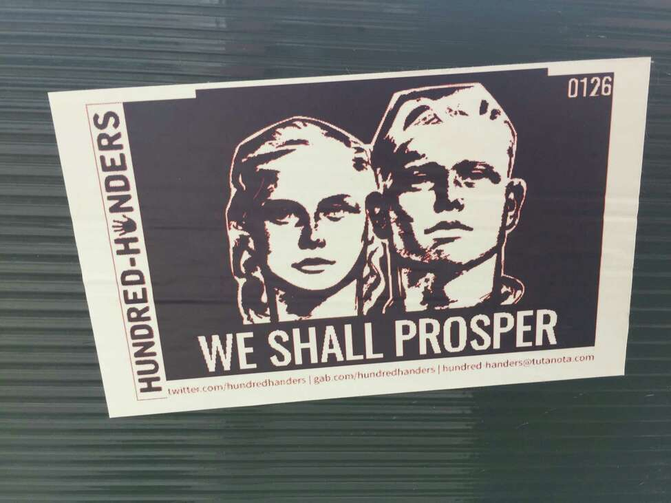 A sticker linked to online white supremacist group Hundred Handers is seen outside Troy City Hall in late June, 2019.