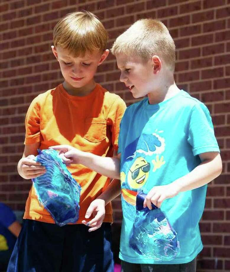 Henry Samet, of Edwardsville, (left) and Caleb Peksa, of Troy, examine each other's animal mask creations during the drying process. Photo: Courtesy Of SIUE