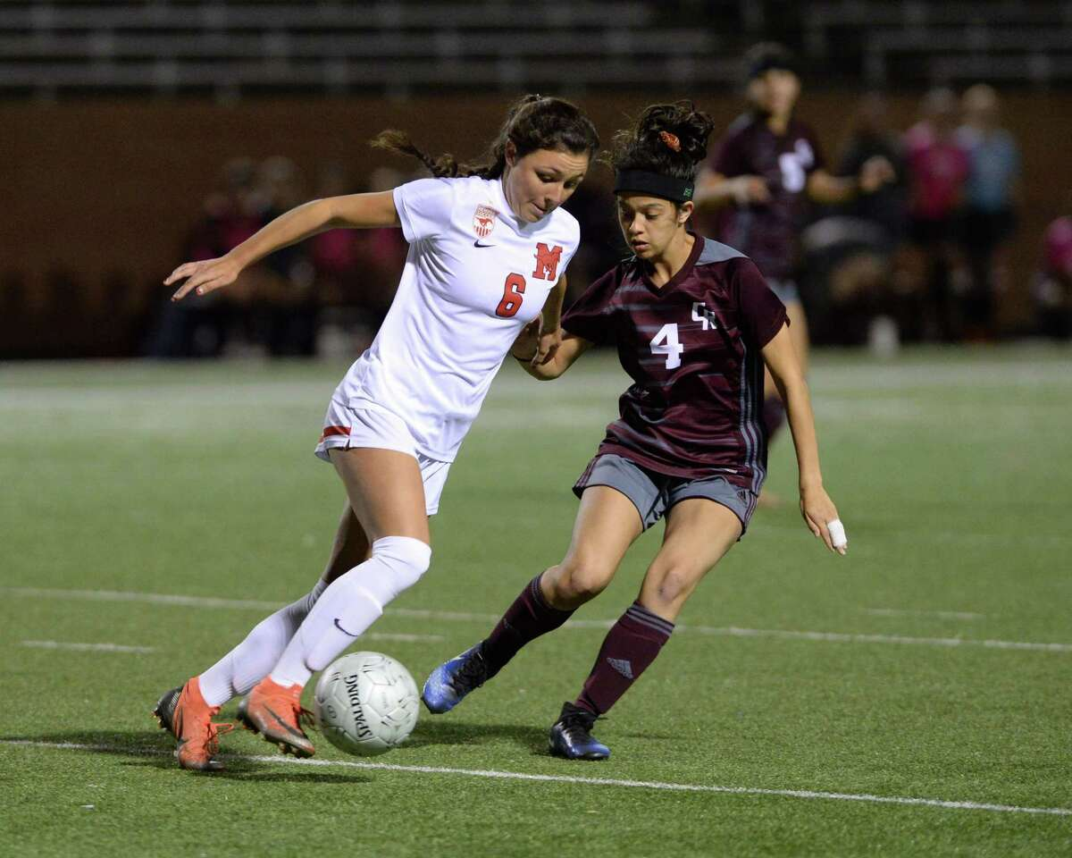 Kelsey Hranicky (6) of Memorial dribbles around Sara Naranjo (4) of Cinco Ranch during the first half of Region III Area Round soccer playoff match between the Cinco Ranch Cougars and the Memorial Mustangs on Tuesday, April 2, 2019 at Rhodes Stadium, Katy, TX.