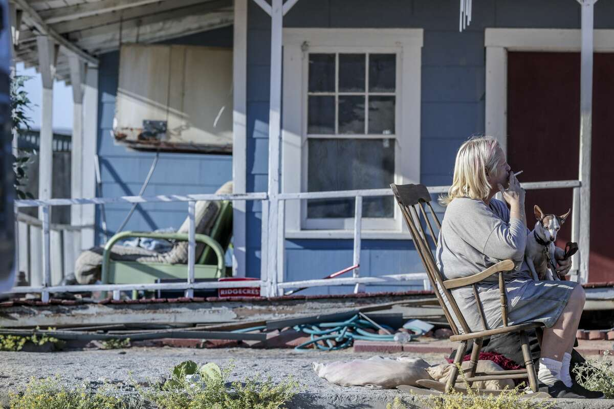 Jamie L. Acevedo sits outside her severely damaged home, waiting to evacuate to Ridgecrest the morning after a 7.1 magnitude earthquake knocked her home off its foundation on July 6, 2019 in Trona, California. (Photo by Robert Gauthier/Los Angeles Times via Getty Images)