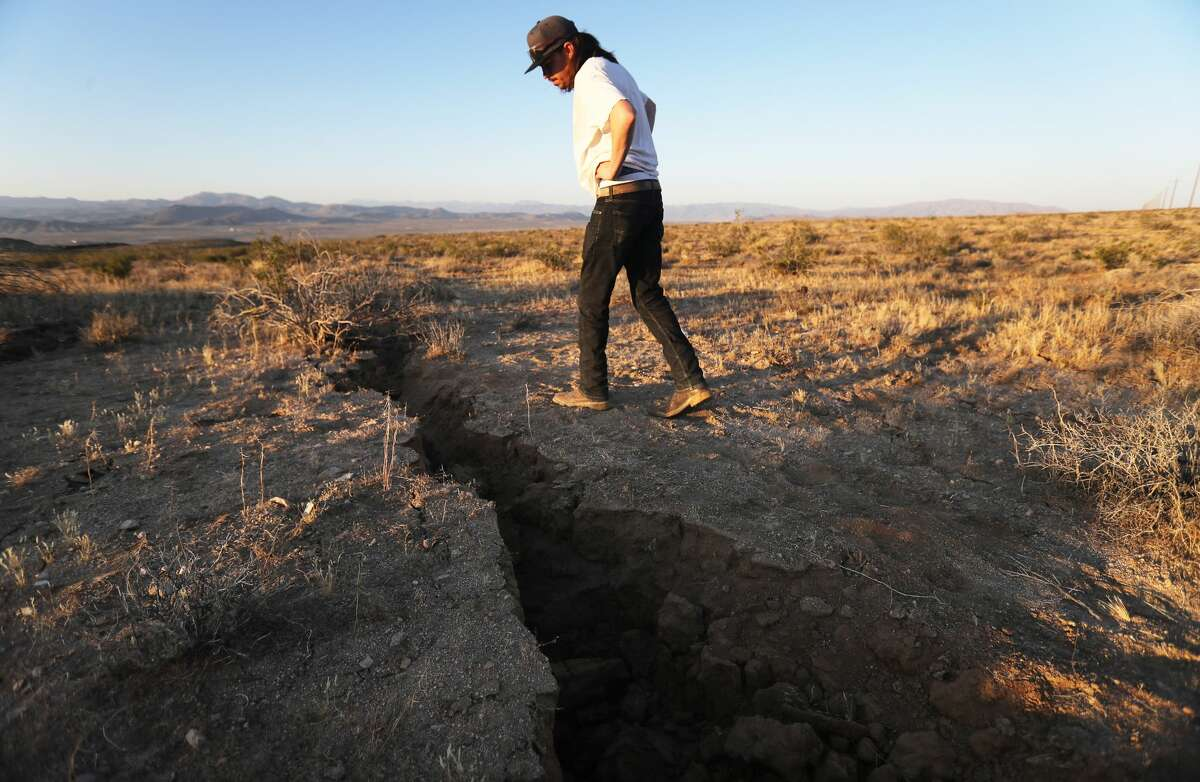 A local resident inspects a fissure in the earth after a 6.4 magnitude earthquake struck the area on July 4, 2019 near Ridgecrest, California. The earthquake was the largest to strike Southern California in 20 years with the epicenter located in a remote area of the Mojave Desert. The temblor was felt by residents across much of Southern California. (Photo by Mario Tama/Getty Images)