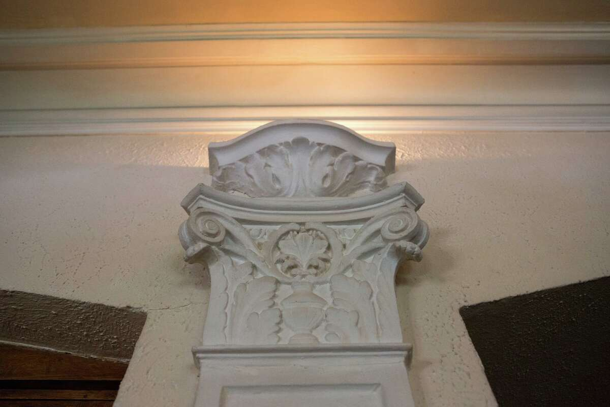 One of the original details that remain in the living area include four vertical friezes, two flanking the fireplace and two book-ending the opposing window. All are topped with lighted sconces, although only the two on the fireplace side work.