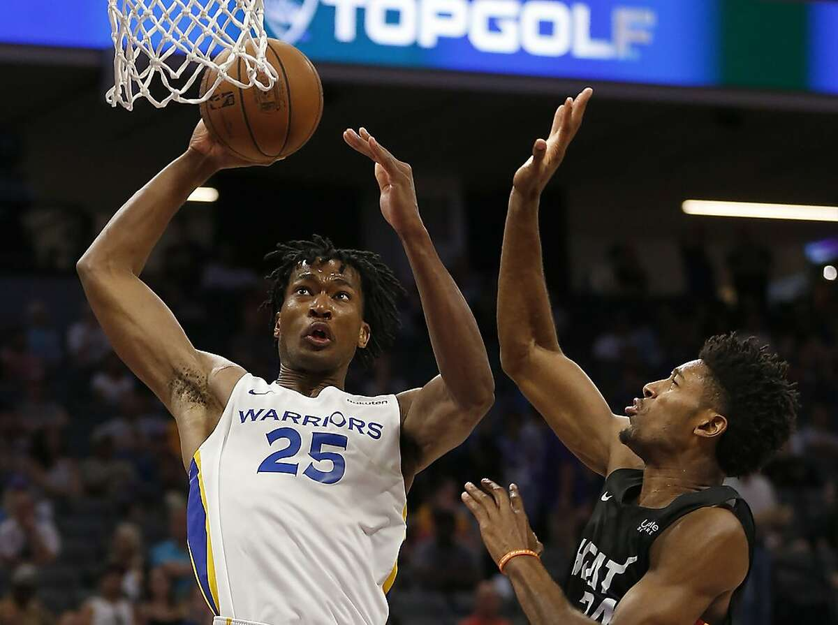 Golden State Warriors center Damian Jones, left, goes to the basket against Miami Heat forward Kyle Alexander during the second half of an NBA basketball summer league game in Sacramento, Calif., Wednesday, July 3, 2019. (AP Photo/Rich Pedroncelli)