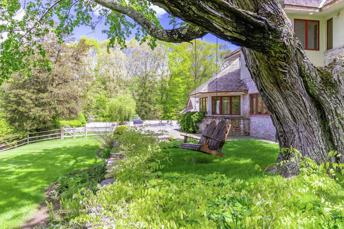 The partially fenced 10.62-acre property features a large bluestone terrace, professional landscaping, and a tree swing for two.