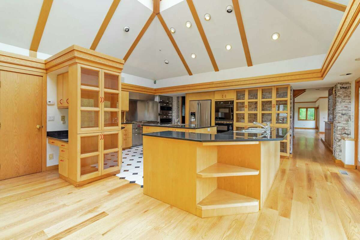 The kitchen features two center islands/breakfast bars, glass-front cabinetry, and a vaulted, beamed ceiling.