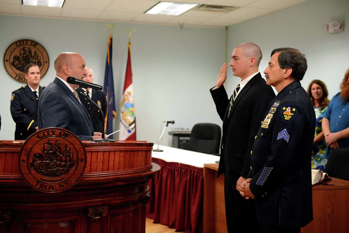 Troy Mayor Patrick Madden, left, swears in Nico Carello, center, who is accompanied by his father, Sgt. Salvatore Carello, right, on Monday, July 8, 2019, at Troy City Hall in Troy, N.Y. (Catherine Rafferty/Times Union)