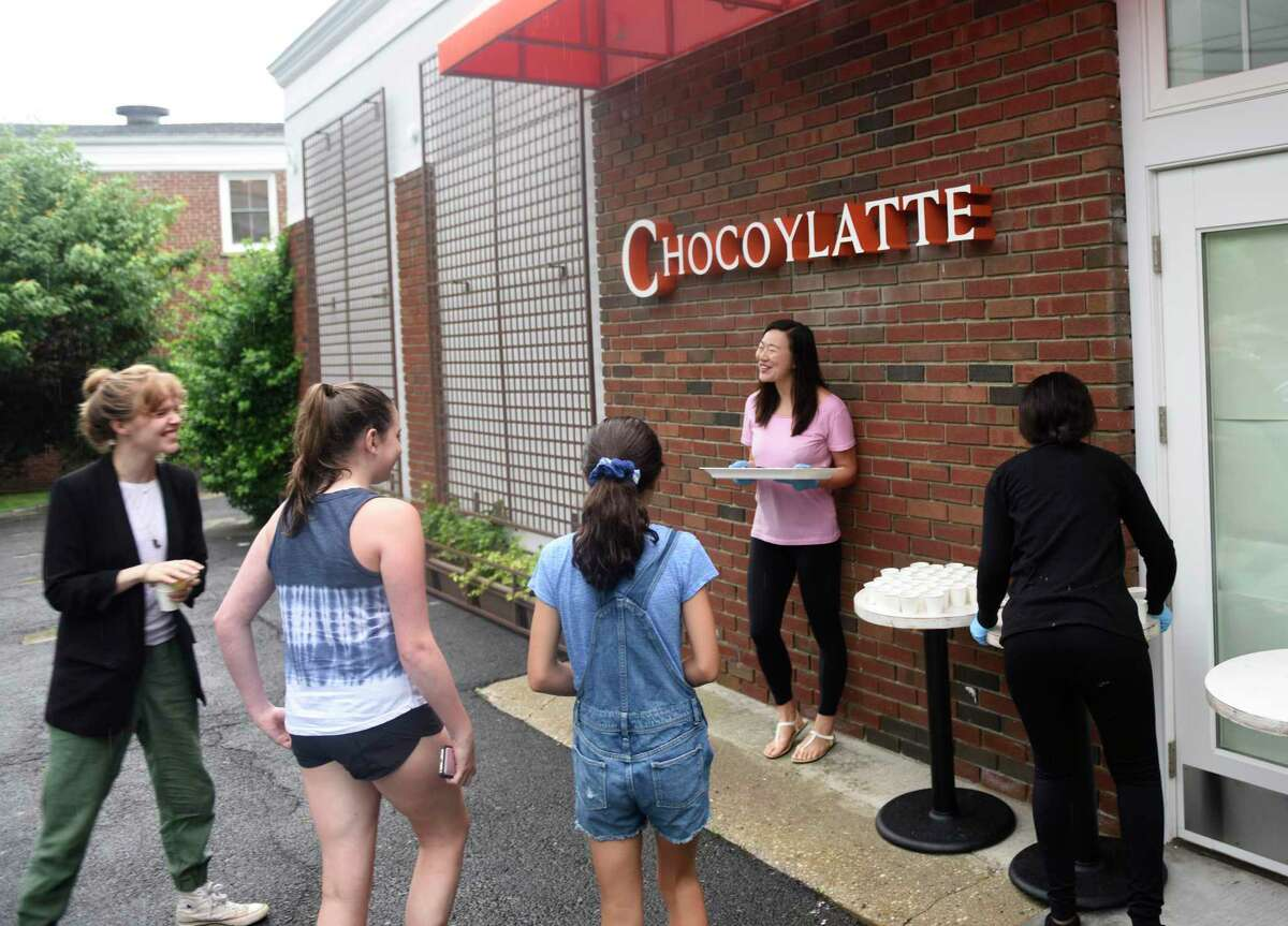 Jing Wu hands out free chocolate and cakes samples outside the new Chocoylatte Gourmet in the Cos Cob section of Greenwich, Conn. Monday, July 8, 2019. The official opening and ribbon-cutting was delayed due to an electrical issue, but folks still stopped by to receive samples and chat with employees.