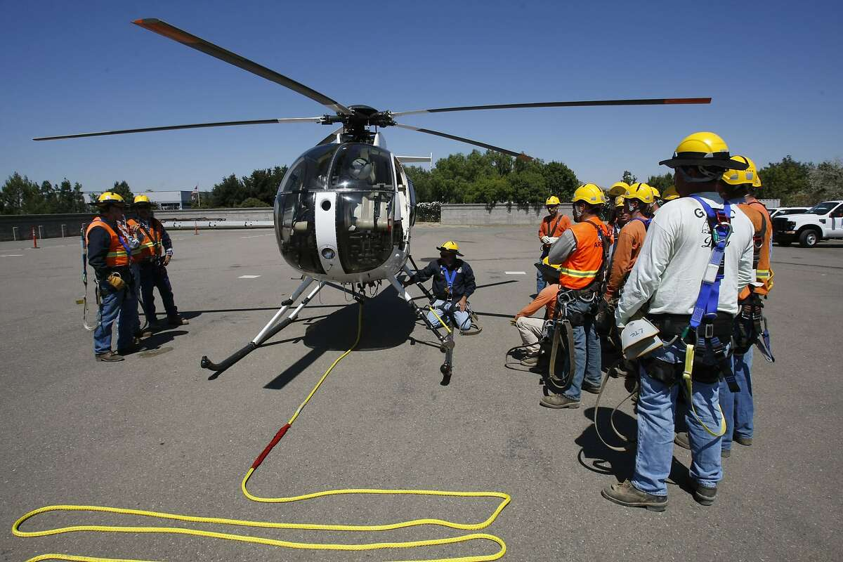 PG&E training instructor Pat Windschitl, kneeling next to the helicopter, gives a safety briefing during a training session where linemen learned how to be transported by helicopter to transmission towers.