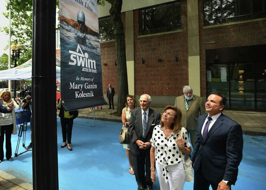 From left; Roseanne Ganim, George Ganim, Sr., Josephine Ganim, and Bridgeport Mayor Joe Ganim, admire a SWIM Across the Sound banner in honor of their sister and daughter, Mary Ganim Kolesnick, during the kickoff of the charity's Paint the City Blue campaign on Bank Street in Bridgeport on Monday, July 8, 2018. Ganim Kolesnick passed away after a battle with ovarian cancer. Photo: Brian A. Pounds / Hearst Connecticut Media / Connecticut Post