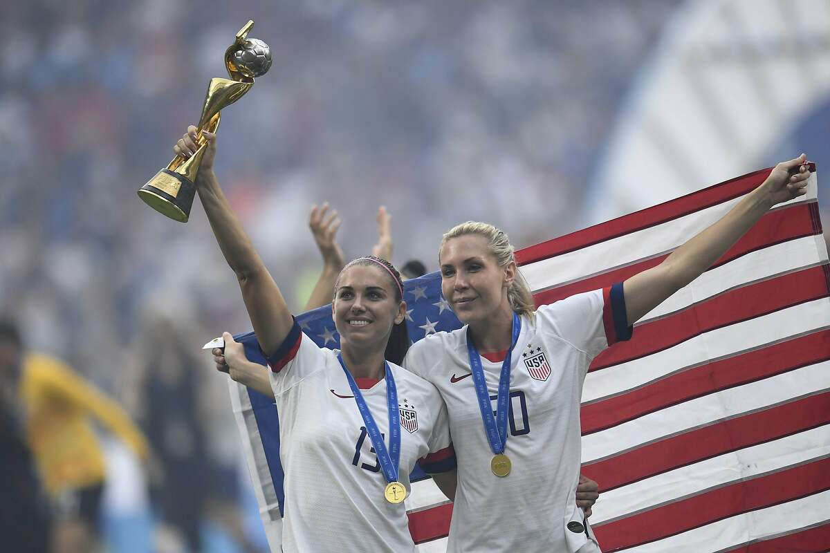 United States' forward Alex Morgan (L) and United States' midfielder Allie Long celebrate with the trophy after the France 2019 Women's World Cup football final match between USA and the Netherlands, on July 7, 2019, at the Lyon Stadium in Lyon, central-eastern France.