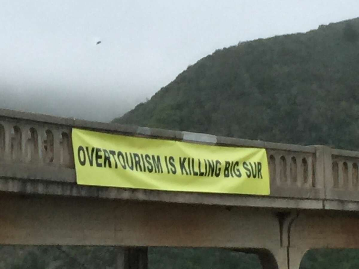 """A banner reading """"OVERTOURISM IS KILLING BIG SUR"""" hangs from Bixby Bridge in July 2019."""