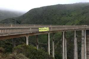 "A banner reading ""OVERTOURISM IS KILLING BIG SUR"" hangs from Bixby Bridge in July 2019."
