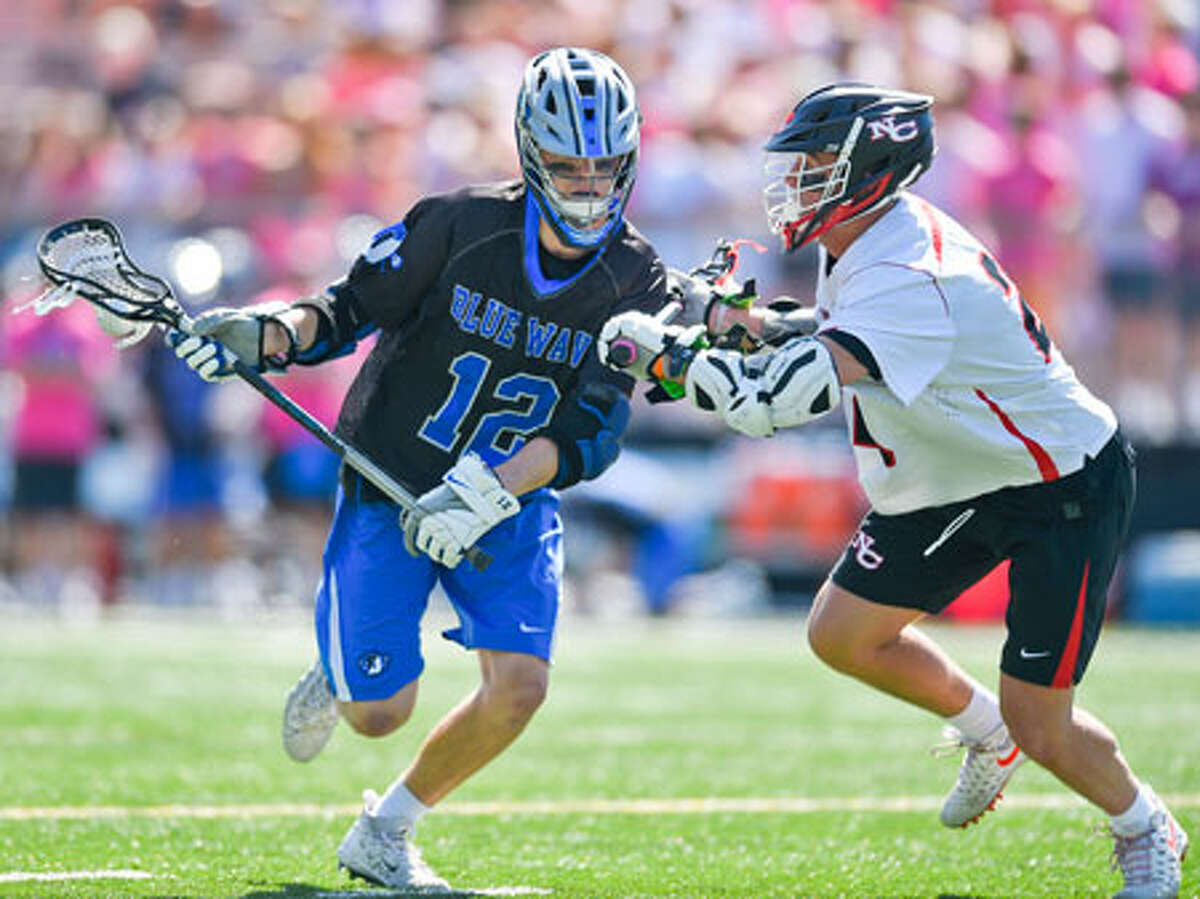 Darien's Tommy Hellman drives upfield against New Canaan's Christian Sweeney (24) during the Wave's 12-3 win over their rivals at Duning Field on May 11. - Matthew Brown/Hearst Connecticut Media