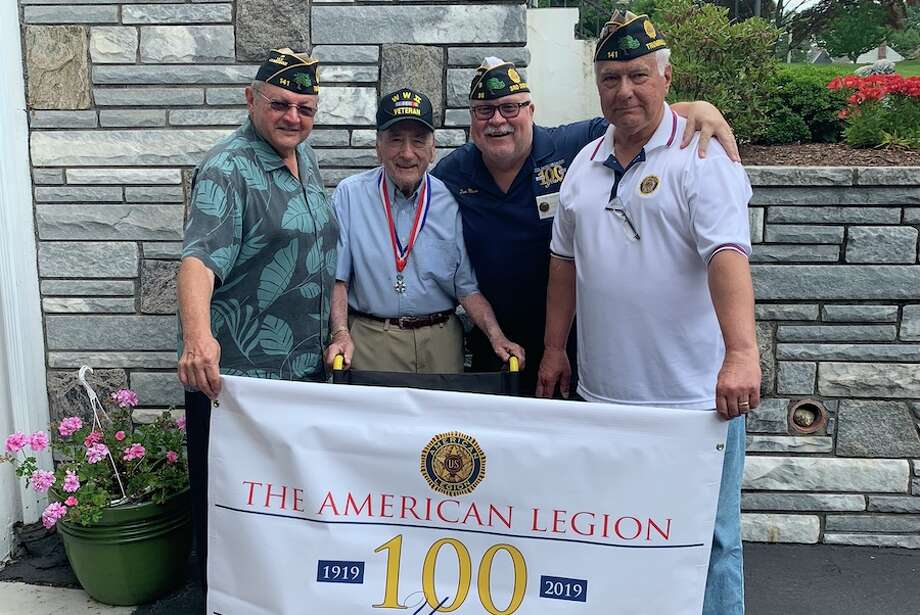 At the presentation of a wheelchair are, from left, Joe Montanaro (Senior VicecCommander of Post 141), Anthony Salce (World War II veteran and Post 141 member), Tom Moore (Adjutant of Post 86), and Ernie Foito (Commander of Post 141).