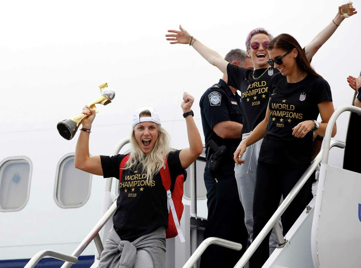Members of the United States women's soccer team, winners of a fourth Women's World Cup, including Julie Ertz, left, Megan Rapinoe, top center, and Alex Morgan, top right, celebrate after arriving at Newark Liberty International Airport, Monday, July 8, 2019, in Newark, N.J.