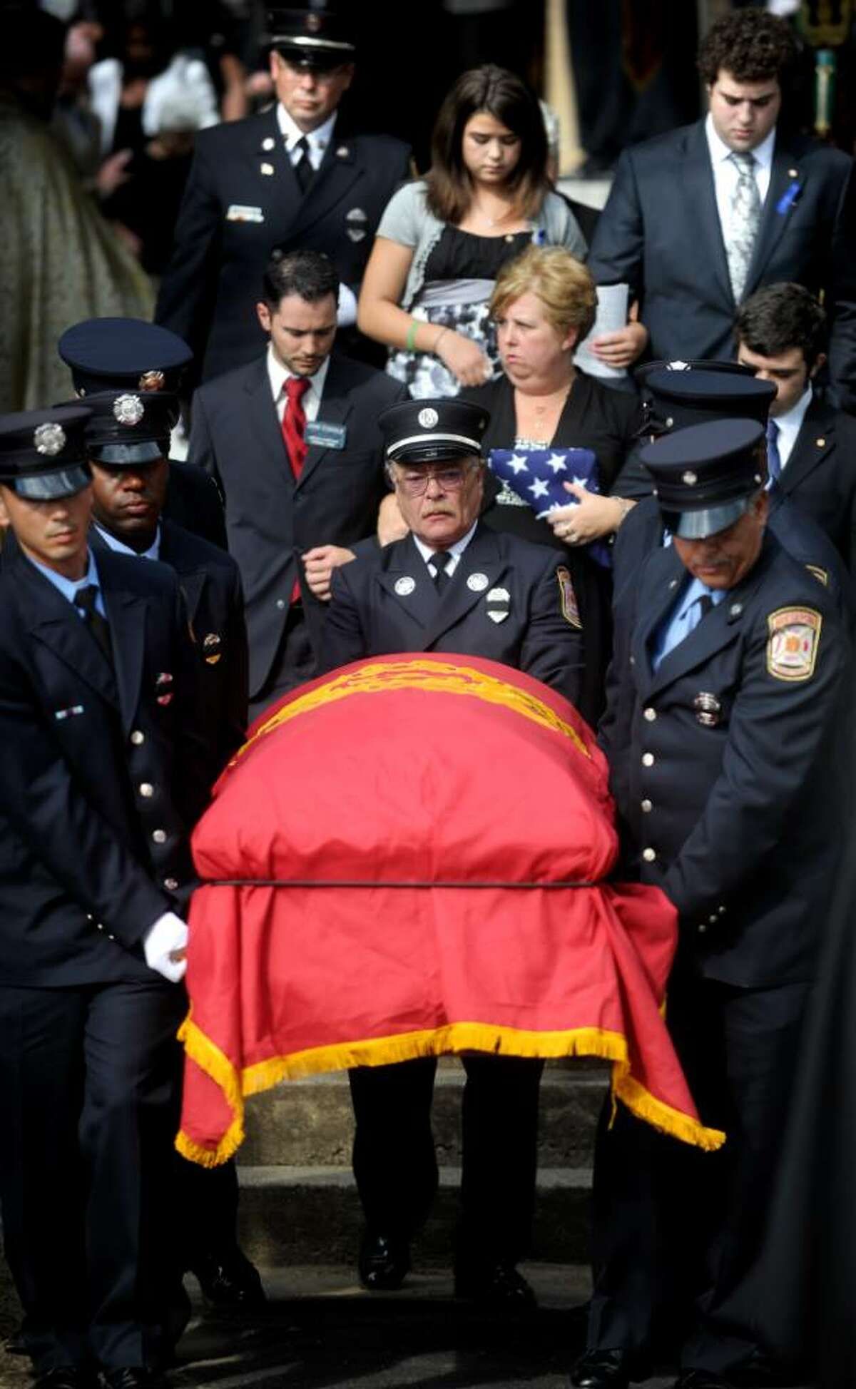Firefighters carry the casket of Michel Baik as his wife and children follow down the steps of St. Nicholas Antiochian Orthodox Church in Bridgeport on Friday, July 30, 2010.